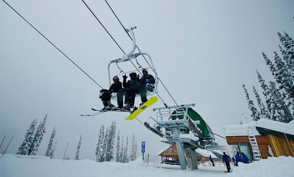 people sitting on a chairlift and waving